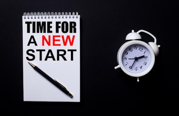Zeit für einen neuen start geschrieben in einem weißen notizblock in der nähe eines weißen weckers