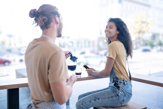 Zeit für kaffee. glückliche frau im jeansoverall, der im café nahe großem fenster und mann in der schürze mit kaffeekanne sitzt