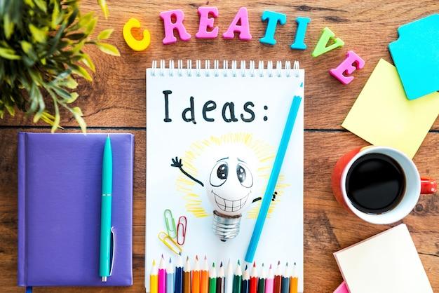 Zeit für kreative ideen. draufsicht auf notizblock mit kaffeetasse auf dem holzschreibtisch