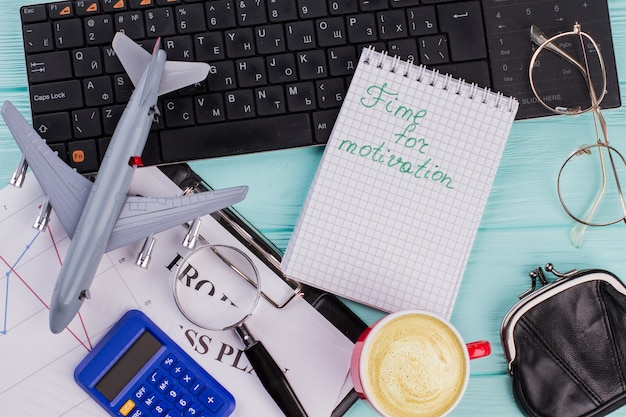 Zeit für motivation auf notebook mit bürozubehör und flugzeug auf holztischplattenhintergrund. flache zusammensetzung.