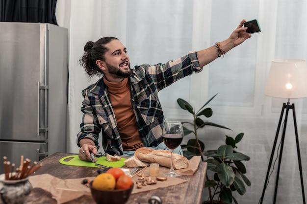 Zeit für's abendessen. angenehmer netter mann, der selfies macht, während er in der küche ist