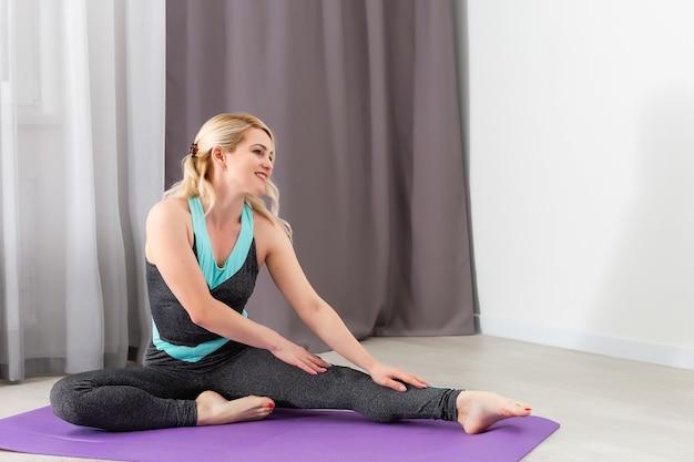 Zeit für yoga. attraktive und gesunde junge frau, die übungen macht, während sie sich zu hause ausruht