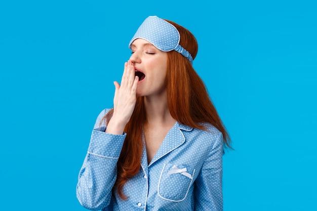 Zeit fürs bett. schläfrige und müde süße sinnliche weibliche rothaarige frau in nachtwäsche