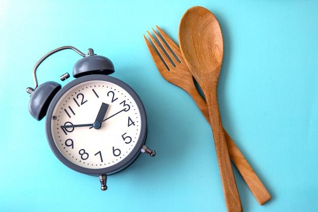 Zeit, gewicht zu verlieren, kontrolle zu essen oder zeit, konzept, wecker mit einer gesunden werkzeugkonzeptdekoration auf blauem hintergrund zu nähren