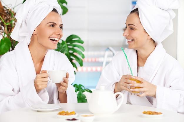 Zeit im spa verbringen. zwei schöne junge frauen im bademantel, die tee trinken und miteinander sprechen, während sie vor dem schwimmbad sitzen