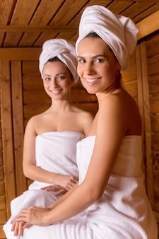 Zeit in der sauna verbringen. zwei attraktive frauen, die in ein handtuch gewickelt in der sauna sitzen und dir zulächeln