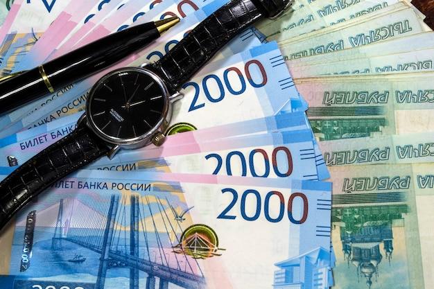 Zeit ist geld da ist eine schwarze uhr und ein schwarzer stift auf dem geld