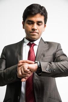 Zeit ist geld konzept - indischer asiatischer junger geschäftsmann, der zeit in seiner armbanduhr sucht oder einstellt, isoliert auf weißem hintergrund stehend