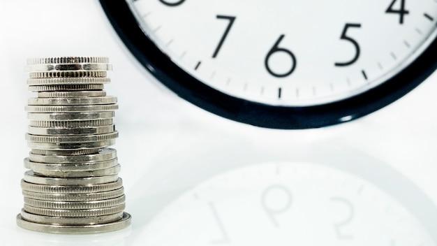 Zeit ist geld konzept: wecker und mit münzen