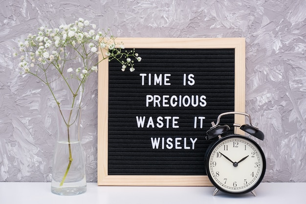 Zeit ist wertvoll, verschwende sie sinnvoll. motivzitat auf briefpapier, schwarzer wecker, blume im vase auf tabelle