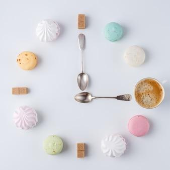 Zeit, kaffee zu trinken. eine uhr in form von kaffee. macarons, zucker, marshmallows. kreative und kreative arbeit.