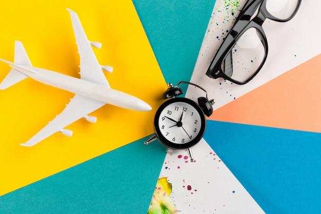 Zeit, konzept zu reisen. plastikflugzeug jet spielzeug passagier mit wecker