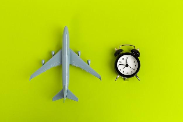 Zeit, konzept zu reisen. plastikflugzeug jet toy passagier mit wecker
