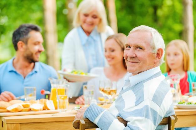 Zeit mit der familie genießen. glückliche fünfköpfige familie, die draußen am esstisch sitzt, während ein älterer mann über die schulter schaut und lächelt
