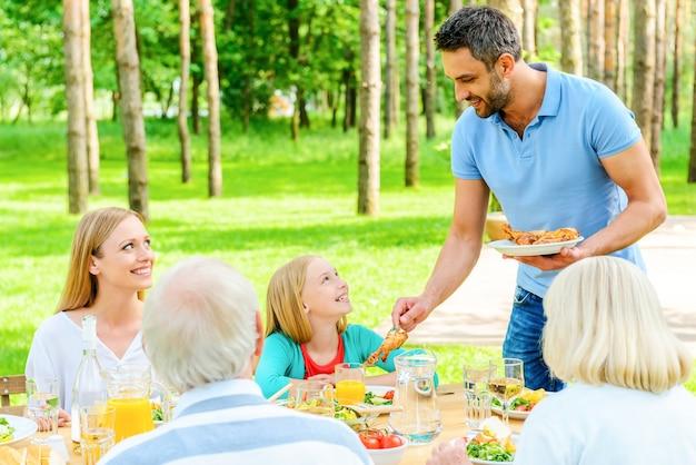 Zeit mit der familie genießen. glückliche fünfköpfige familie, die gemeinsam am esstisch im formalen garten sitzt?