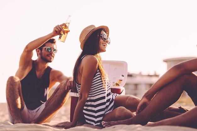 Zeit mit freunden verbringen. fröhliche junge leute verbringen schöne zeit miteinander, während sie am strand sitzen und bier trinken
