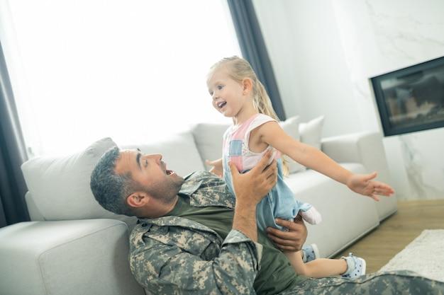 Zeit mit papa. tochter fühlt sich involviert, während sie zeit mit papa verbringt, der nach dem militärdienst nach hause kommt