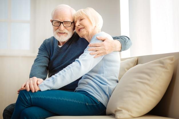 Zeit mit vergnügen. glücklicher rentner, der beiseite schaut und ein lächeln auf seinem gesicht behält, während er seine frau umarmt