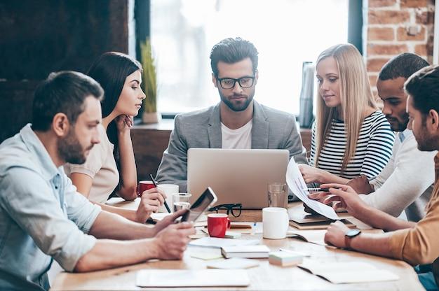 Zeit, sich mit dem neuen businessplan vertraut zu machen! eine gruppe von sechs jungen leuten, die im büro am tisch sitzend, lesen und schauen, warf diagramme