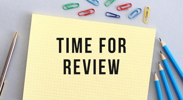 Zeit, text im notizbuch auf grauem hintergrund neben bleistiftstift und büroklammern zu überprüfen