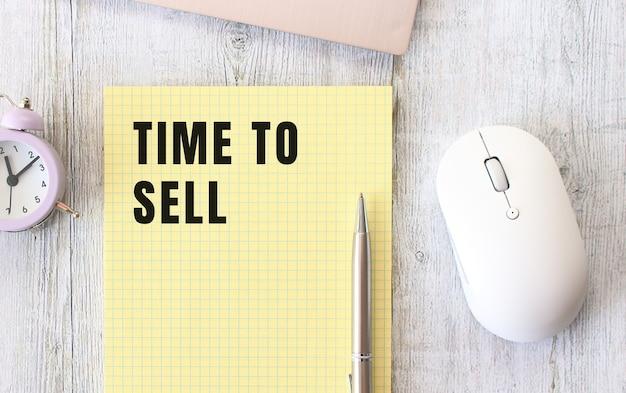 Zeit, text zu verkaufen, der in einem notizbuch geschrieben ist, das auf einem hölzernen arbeitstisch neben einem laptop liegt. unternehmenskonzept.