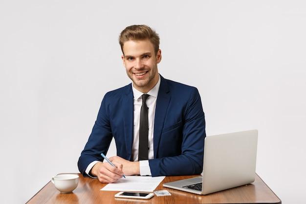 Zeit um geld zu verdienen. der schöne bürovorsteher, der seinen schreibtisch sitzt, bericht und lächelnden antwortenden kunden schreibt, behälter, bereiten dokumentation vor und verwenden laptop, trinken kaffee von der schale