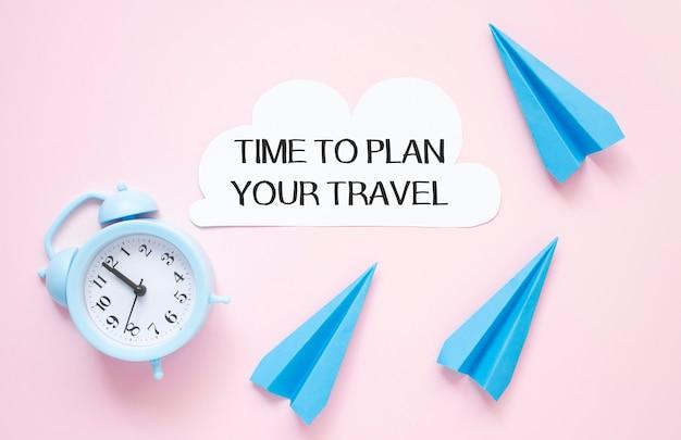 Zeit, um ihren reisetext auf papier mit uhr und papierflugzeug auf einem rosa tisch zu planen.