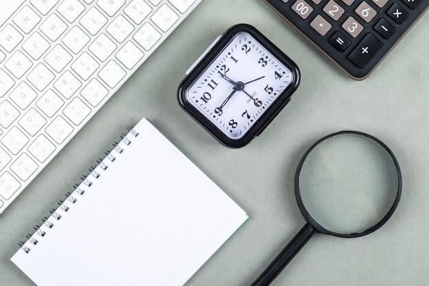 Zeit- und geldkonzept mit tastatur, taschenrechner, lupe, notizbuch, uhr auf dunkelgrünem hintergrund draufsicht. horizontales bild