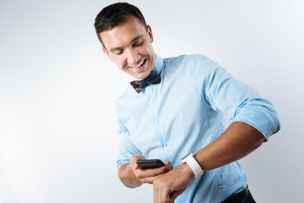 Zeit vergleichen. positiv entzückter junger mann, der auf seine smartwatch schaut und sein smartphone hält, während zeit vergleicht