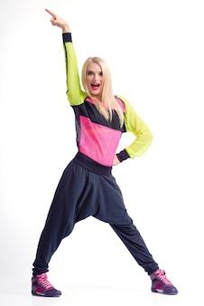 Zeit zu gehen. vertikale studioaufnahme in voller länge einer fröhlichen blonden tänzerin in sportkleidung, die aufgeregt schreit und den arm isoliert in die luft hebt