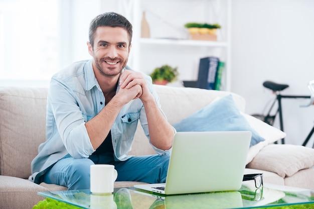 Zeit zu hause genießen. hübscher junger mann, der in die kamera schaut und lächelt, während er zu hause auf der couch sitzt, während der laptop in seiner nähe liegt?