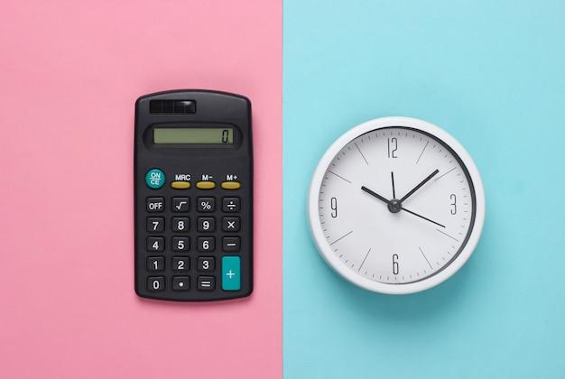 Zeit zu investieren. weiße uhr und taschenrechner auf blauem rosa hintergrund. minimalistische studioaufnahme. draufsicht