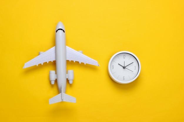 Zeit zu reisen. flugzeugfigur und uhr auf gelber fläche. draufsicht Premium Fotos