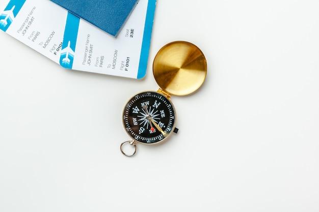 Zeit zu reisen. ideentourismus mit flugtickets und kompass auf weiß