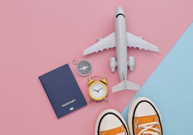 Zeit zu reisen. reisezubehör auf rosa blauem pastellhintergrund. abenteuer. flach liegen.