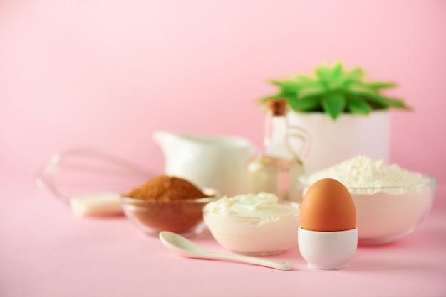Zeit zum backen. backzutaten - butter, zucker, mehl, eier, öl, löffel, pinsel, schneebesen, milch über rosa hintergrund. bäckereilebensmittelrahmen, konzept kochend. kopieren sie platz