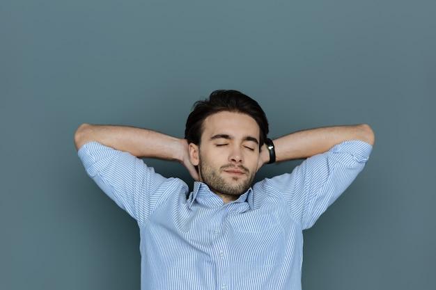 Zeit zum entspannen. angenehmer netter gutaussehender mann, der seine augen schließt und sich ausruht, während er hände unter seinen kopf legt Premium Fotos