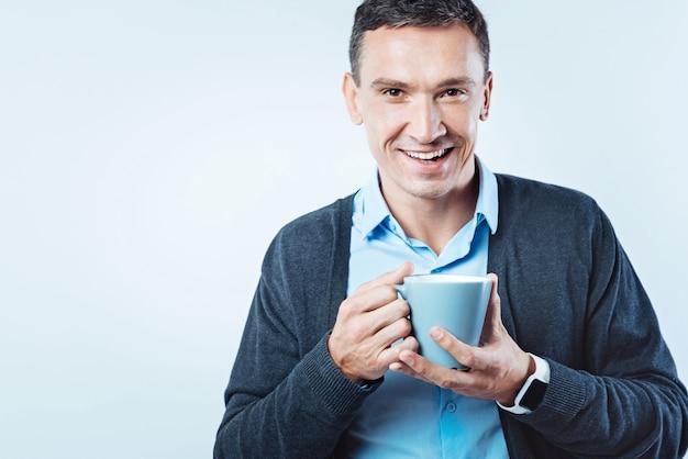 Zeit zum entspannen. freundlich aussehender reifer kerl, der in die kamera mit einem fröhlichen lächeln auf seinem gesicht schaut, während er seine tasse kaffee über dem hintergrund genießt.