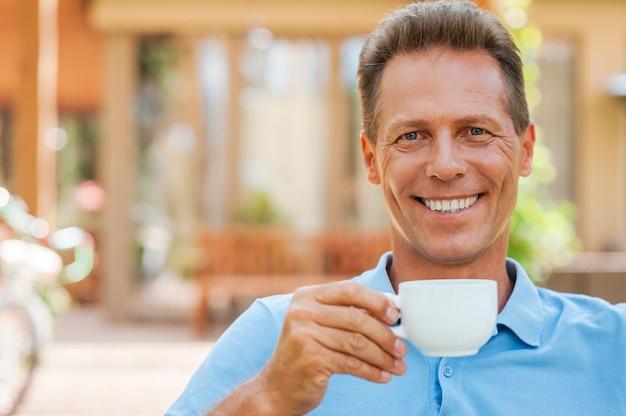 Zeit zum entspannen. fröhlicher reifer mann, der kaffee trinkt und lächelt, während er draußen mit haus im hintergrund sitzt