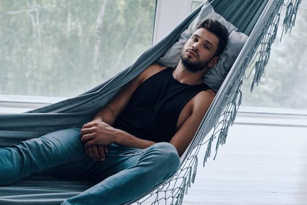 Zeit zum entspannen. hübscher junger mann in freizeitkleidung, der die kamera anschaut, während er drinnen in der hängematte liegt