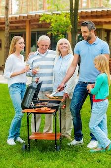 Zeit zum grillen. in voller länge von der glücklichen familie, die fleisch auf dem grill im freien grillt
