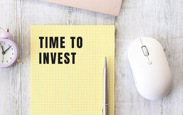 Zeit zum investieren von text, der in ein notizbuch geschrieben ist, das auf einem hölzernen arbeitstisch neben einem laptop liegt. unternehmenskonzept.