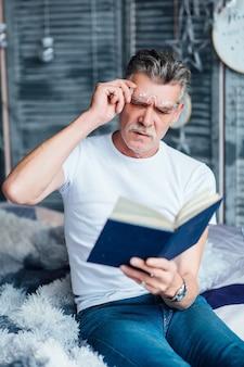 Zeit zum reden älterer bärtiger mann mit seinem lieblingsbuch, der auf dem sofa sitzt