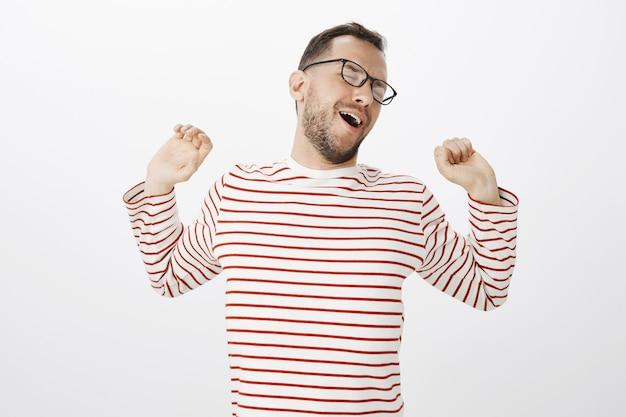 Zeit zum strippen nach einem produktiven arbeitstag. porträt des müden entspannten attraktiven europäischen mannes im gestreiften hemd, die hände zurückziehen, während sie strippen und gähnen