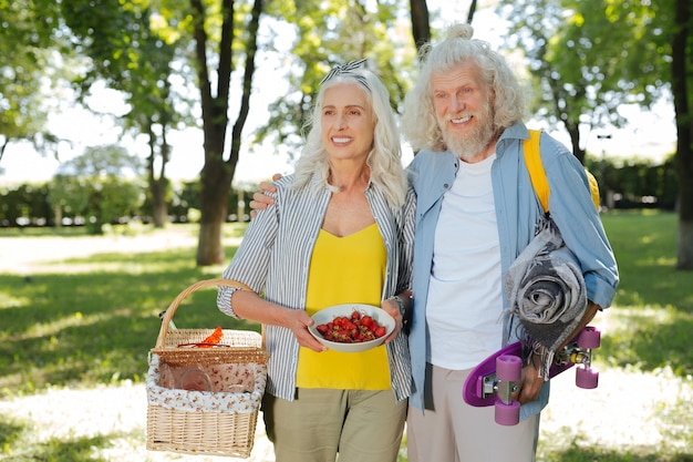 Zeit zusammen. positiver alter mann, der umarmt, ist frau, während sie mit ihr ein picknick macht