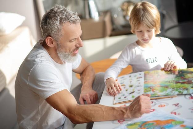 Zeit zusammen verbringen. ein älterer mann und ein junge, die zusammen ein buch lesen