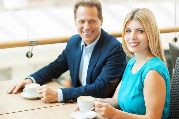 Zeit zusammen verbringen. schönes reifes paar, das zusammen kaffee trinkt und beim sitzen im café in die kamera schaut?