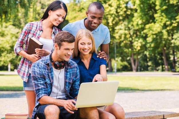 Zeit zusammen verbringen. vier glückliche junge leute diskutieren etwas und schauen auf den laptop, während sie zusammen im freien sitzen