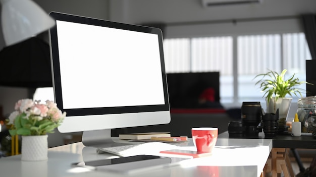 Zeitgemäßer arbeitsbereich mit computer- und büromaterial auf weißem schreibtisch.