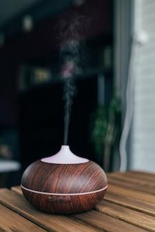 Zeitgemäßer intelligenter luftbefeuchter auf dem tisch, der wasserdampf emittiert